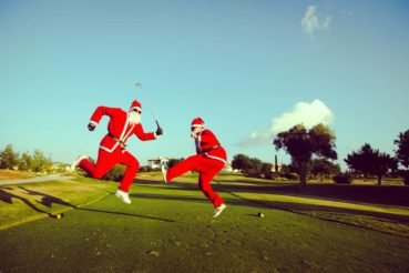 Two Santa Claus jumping on a golf course
